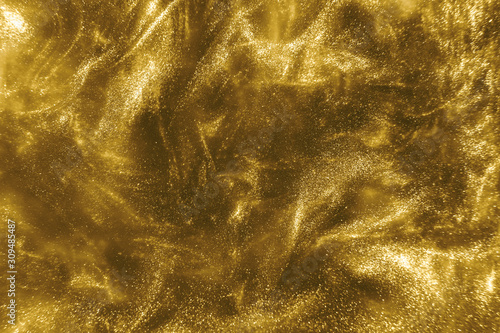Obraz Abstract elegant, detailed gold glitter particles flow with shallow depth of field underwater. Holiday magic shimmering luxury background. Festive sparkles and lights. de-focused. - fototapety do salonu