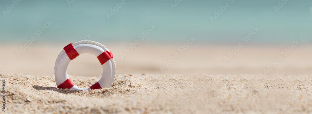 Fototapeta Lifebuoy On Sand At Beach