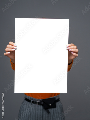 Ταπετσαρία τοιχογραφία Stylish teen girl young with big paper sheet in her hands on gray background