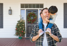 Boy Riding Piggyback On Shoulders Of Father On Christmas Decorated Front Porch