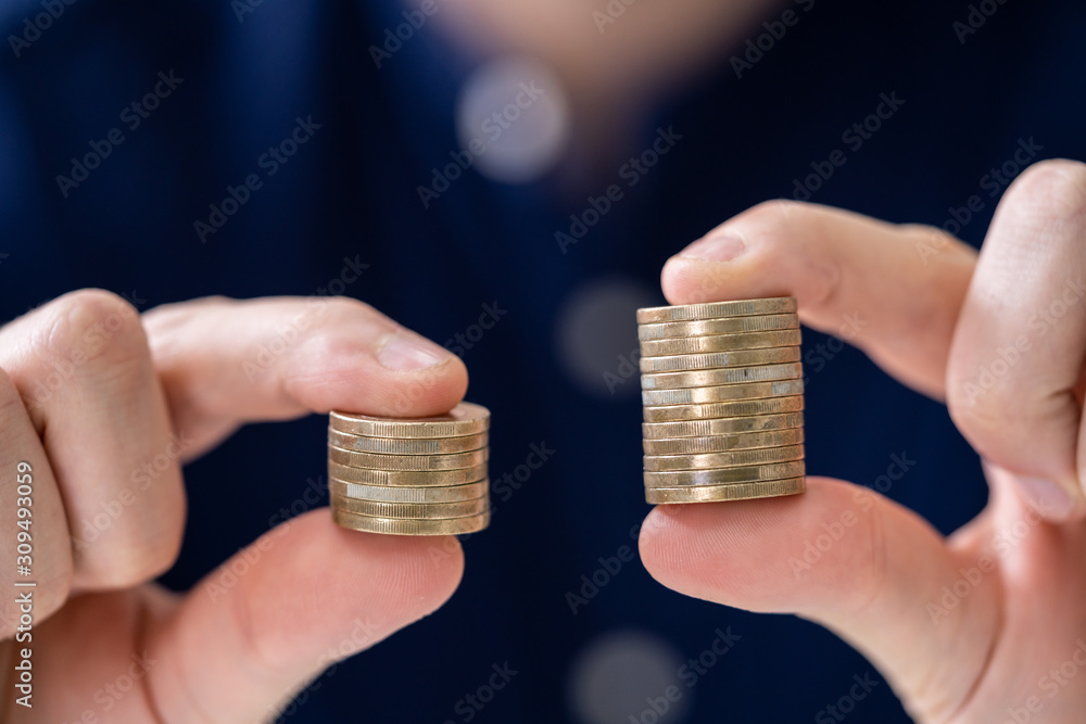 Fototapeta Man Holding Two Coin Stacks