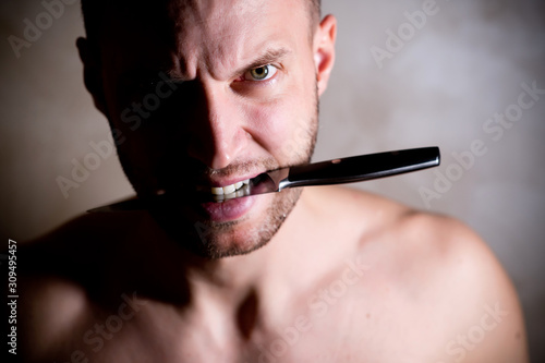 Fényképezés  man holding a knife in his teeth