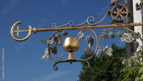 Medieval guild sign for a restaurant and wine cellar showing a golden wine goblet surrounded by wine leaves Canvas Print