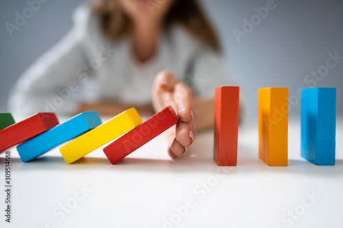 Photo Businessperson Hand Stopping Colorful Blocks From Falling