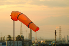 Orange Windsock On Sunset Sky And Industrial Estate Background