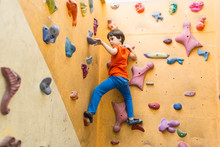 Boy Climbing On Artificial Bou...