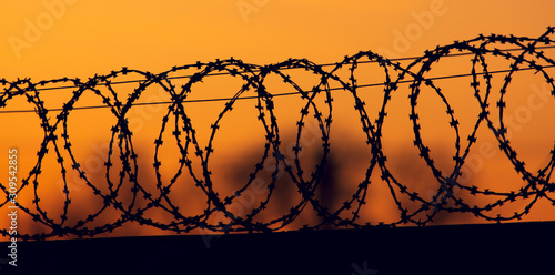 Photo barbed wire on the fence against the backdrop of the sunset.