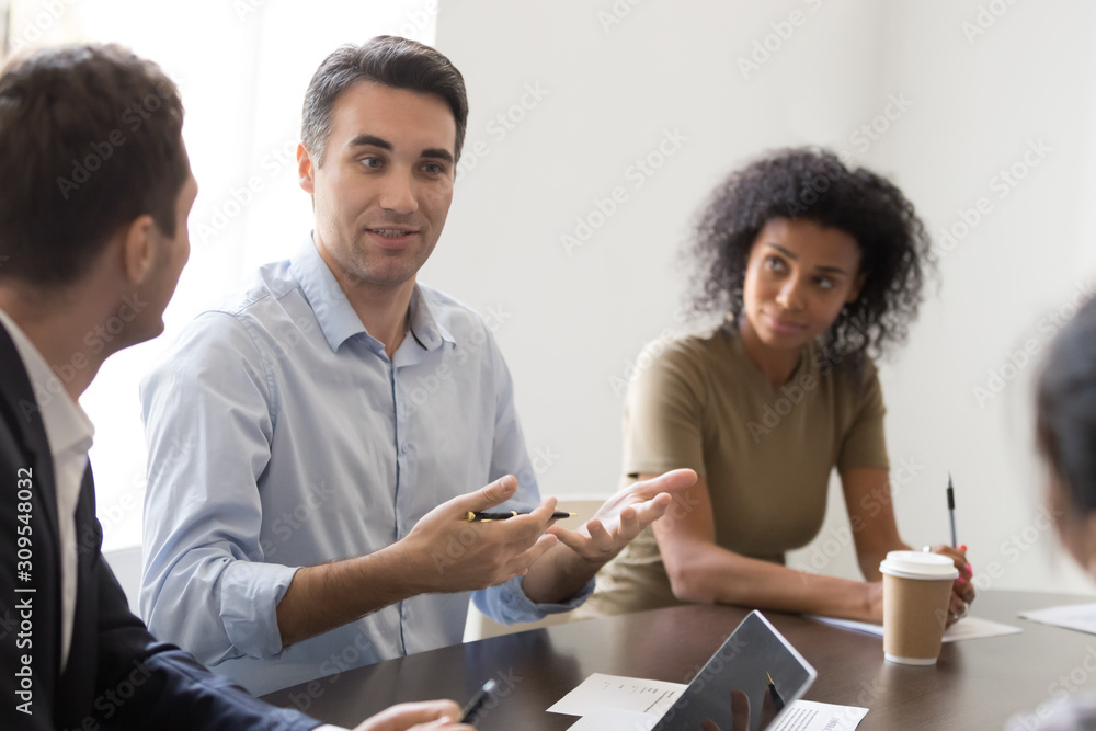 Fototapeta Confident businessman sharing thoughts with colleagues at morning briefing