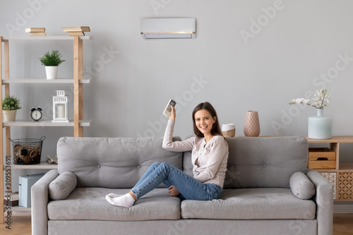 Photo Smiling girl relax on couch turn on air conditioner