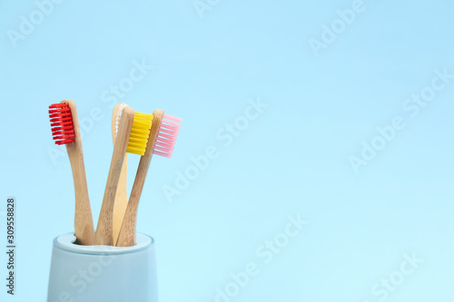 Valokuva Toothbrushes made of bamboo in holder on light blue background