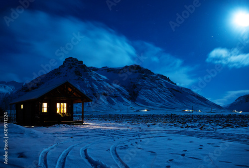 Photo Landscape with a wooden house with light from the window in a winter night