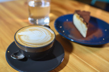 Snickers Cheesecake On A Blue Saucer, A Glass Of Water And A Cup Of Fresh Cappuccino On A Large Bright Wooden Table