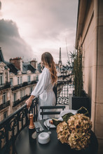 Young Woman With Blonde Hair On Paris Balcony In Front Of Eiffel Tower