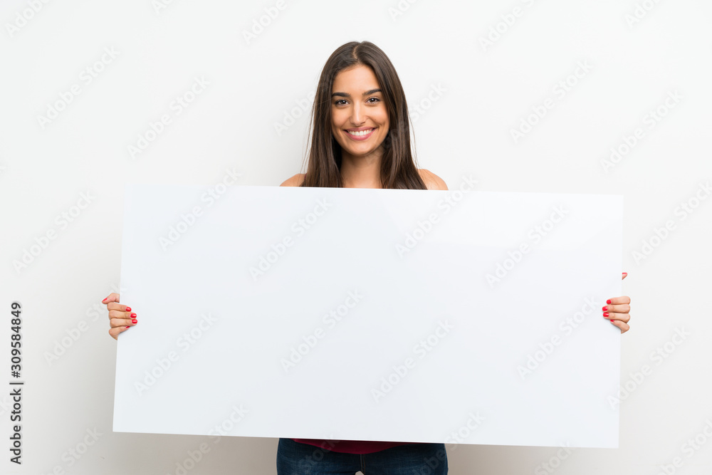 Fototapeta Young woman over isolated white background holding an empty white placard for insert a concept