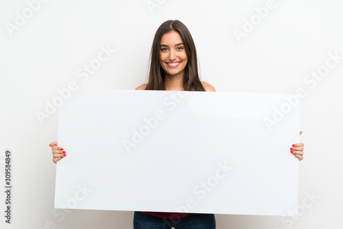 Fototapeta Young woman over isolated white background holding an empty white placard for in