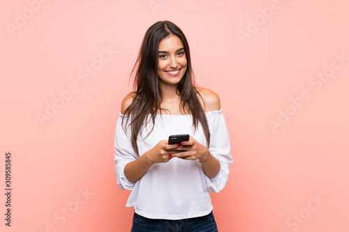 Fototapeta Young woman over isolated pink background sending a message with the mobile obraz