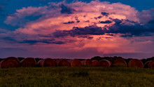 Thunderstorm With Cumulonimbus Clouds Growing Over The Nebraska Countryside And Rows Of Hay During The Sunset.