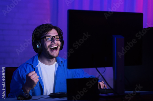 Photo  Overjoyed man win online video game at home