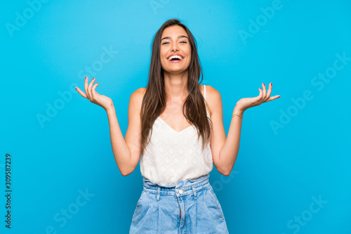 Valokuvatapetti Young woman over isolated blue background smiling a lot