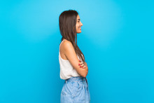 Young Woman Over Isolated Blue Background With Arms Crossed And Looking Forward