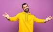 canvas print picture - Handsome man with yellow sweatshirt presenting and inviting to come with hand