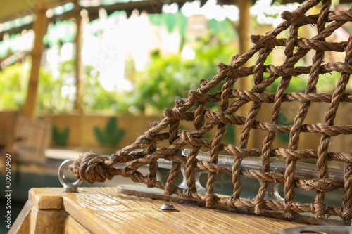 Brown rope is a net attached to the iron ring on the wooden floor Canvas Print