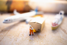 Miniature People: Worker And Brown Paper Box On World Map With Airplane, Ship Using As Background Business Shipping, Rent Container, Worldwide Transportation Concept