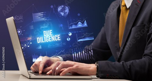 Fototapeta Businessman working on laptop with DUE DILIGENCE inscription, new business conce