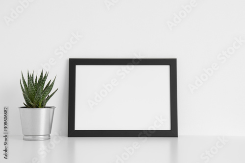Fototapety, obrazy: Black frame mockup with a cactus in a pot on a white table.Landscape orientation.