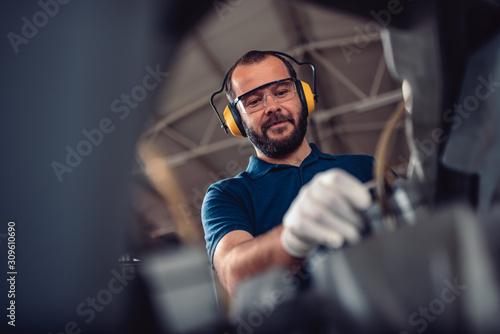 Obraz na plátně Factory worker operating band saw cutting machine