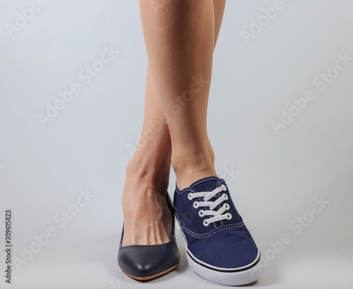 Valokuva Slim woman's legs in two different shoes with heels and sneakers on white background