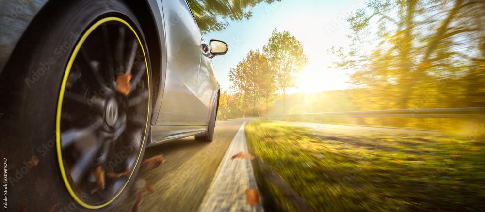 Fototapeta Auto auf einer herbstlichen Landstraße