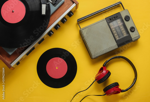 Retro radio receiver, old-fashioned vinyl player, headphones on yellow background Canvas Print