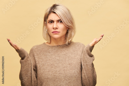Obraz na płótnie Angry perplexed young blonde woman in beige sweater frowning having indignated look, shrugging shoulders trying to figure out what happened, gesturing emotionally