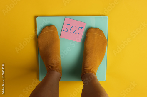 Female legs in socks are standing on the floor scales against yellow background Fototapeta
