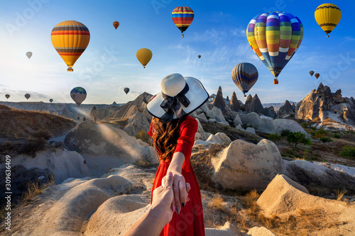 Obraz Women tourists holding man's hand and leading him to hot air balloons in Cappadocia, Turkey. - fototapety do salonu