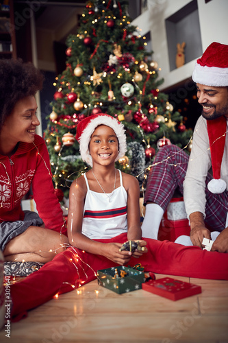 .Girl with parents in front of decorated Christmas tree - 309647097