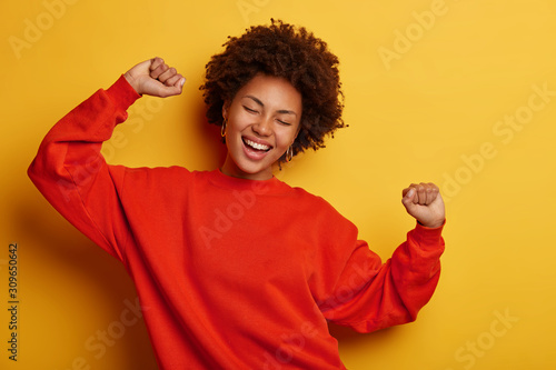 Photo of pleasant looking happy African American woman dances happily, laughs with fun, dressed in casual jumper, isolated over yellow wall, feels entertained. People, happiness, relaxation concept - 309650642