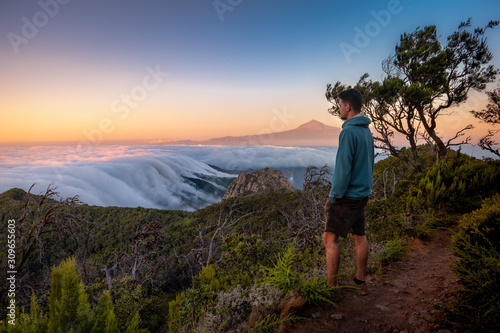 Photo Hombre joven contempla el mar de nubes al atardecer en el Parque Nacional de Garajonay, la Gomera