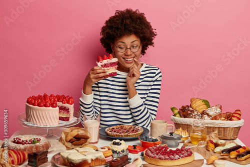 Tela Photo of happy curly haired female holds big piece of strawberry cake, eats yummy desserts on her birthday, has sugar addiction, prepared homemade confectionery, smiles positively