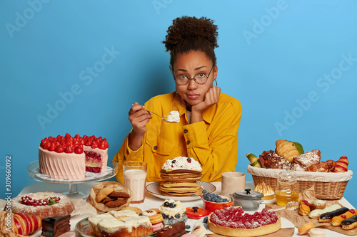 Fotomural Horizontal shot of sad dark skinned woman eats cream from pancakes, eats holiday treats, feels lonely during birthday, eats junk food, doesnt care about figure
