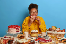 Cheat Meal And Gluttony Concept. Ethnic Curly Woman Eats Strawberry Creamy Cake With Much Calories, Has Sweet Lunch, Tastes Various Desserts, Leads Sweet Life With Confectionery. Female Fan Of Bakery