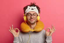 Pleased Guy Makes Oaky Gesture With Both Hands, Meditates During Listening Music, Has Unforgettable Journey, Uses Neck Pillow For Travelling On Long Distance, Feels Relaxed. People, Journey, Yoga, Nap