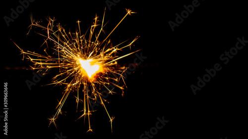 Fotomural Sparkling sparkler on a black background. New Year theme.