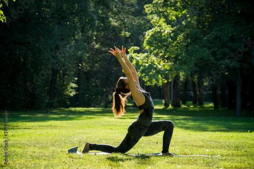 Fotografia young slender woman in jumpsuit practice yoga warrior pose vibrahadrasana on bri