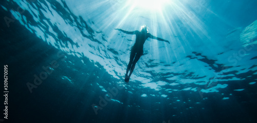 Stampa su Tela Woman floating in the sea and rays of light piercing through