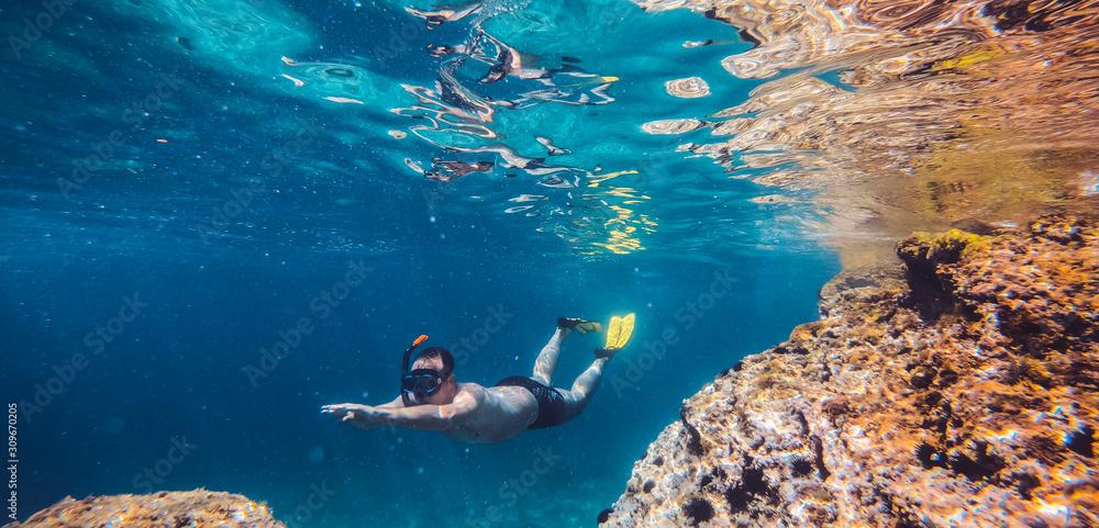 Fototapeta Men snorkeling by the reef