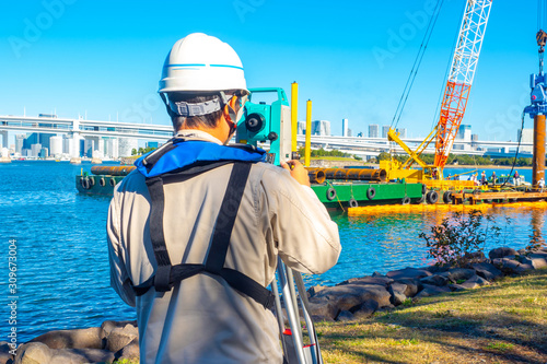 A man works with a theodolite Fototapete