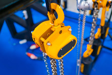 Electric Winch. Metal Winch Chains Lift The Load. Concept - Lifting Heavy Loads. Fragment Of A Yellow Winch. Mechanism For Lifting Weights. Construction Work. Machine For Lifting Or Moving Loads
