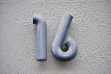 A House Number Plaque, Showing The Number Sixteen (16)